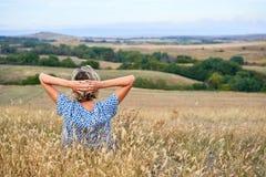 Hintere Ansicht einer Frau, die im trockenen unfruchtbaren Gras, schauend im Horizont sitzt stockbilder