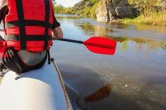 Hintere Ansicht einer Hand mit dem roten Paddel, das auf dem Fluss fl??t stockbilder