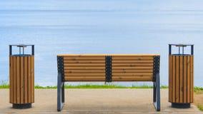 Hintere Ansicht einer Holzbank, die das blaue Wasser gegenüberstellt lizenzfreies stockfoto
