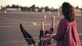 Hintere Ansicht einer jungen Frau, die einen Lebensmittelgeschäftwarenkorb mit ihrer Freundin nach innen im Parken durch das Eink stock footage