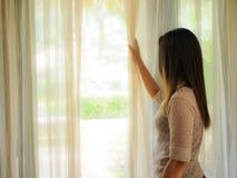 Hintere Ansicht einer jungen Frau, welche die Vorhänge hält, öffnen sich, um aus einem großen hellen Fenster heraus zu Hause zu s Lizenzfreie Stockfotos
