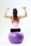 Hintere Ansicht einer jungen Sportfrau, die auf fitball mit dumbells sitzt Lizenzfreie Stockbilder