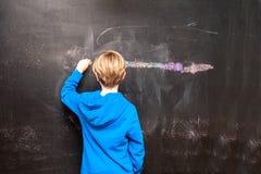 Hintere Ansicht einer Malerei des kleinen Jungen etwas auf einer Tafel Stockbild