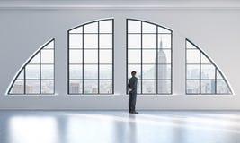Hintere Ansicht einer Person im Gesellschaftsanzug, der heraus das Fenster in einem modernen Dachbodeninnenraum schaut Stockbilder