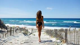 Hintere Ansicht einer schönen jungen Frau, die auf dem Strand aufwirft Ozean, Strand, Sand, Himmelhintergrund stockbild