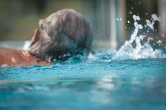 Hintere Ansicht einer Schwimmens des älteren Mannes in einem Pool lizenzfreie stockfotografie