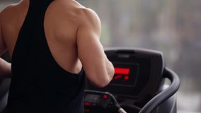 Hintere Ansicht eines athletischen starken Mannes, der auf einer Tretmühle läuft Starke Schultern, Arme und Rückseite Ausarbeiten stock video footage