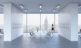 Hintere Ansicht eines Brunette, der heraus das Fenster in einem modernen panoramischen Büro schaut lizenzfreie abbildung