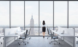 Hintere Ansicht eines Brunette, der heraus das Fenster im modernen panoramischen Büro mit New- Yorkansicht schaut Weiße Tabellen  Stockfoto