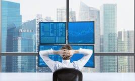 Hintere Ansicht eines entspannenden Händlers, der vor einer Handelsstation sitzt, die aus vier Schirmen mit Finanzdaten besteht A Stockbilder