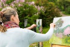 Hintere Ansicht eines Frauenmalers, der draußen im Park oder im Kaimanfisch arbeitet Stockbild