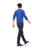 Hintere Ansicht eines gehenden zufälligen Mannes, der zu einer Seite schaut Lizenzfreie Stockbilder