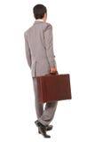 Hintere Ansicht eines Geschäftsmannes, der einen Aktenkoffer steht und hält Stockfoto