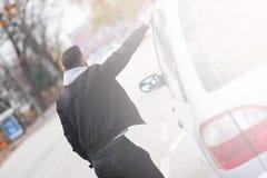 Hintere Ansicht eines Hippie-Mannes, der nahe bei einem Auto steht Lizenzfreies Stockfoto
