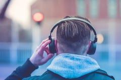 Hintere Ansicht eines Hippie-Mannes mit Kopfhörern Lizenzfreies Stockfoto