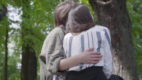 Hintere Ansicht eines jungen gl?cklichen Paars in der zuf?lligen Kleidung Zeit im Park zusammen verbringend, ein Datum habend Lie stock footage