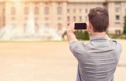 Hintere Ansicht eines jungen Mannes, der Foto macht Stockfotografie
