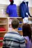Hintere Ansicht eines jungen Paares, das Männer betrachtet, kleidet Stockfotos