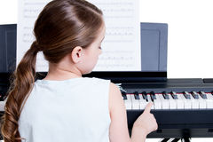 Hintere Ansicht eines kleinen Mädchens, welches das E-Piano spielt. Stockbild