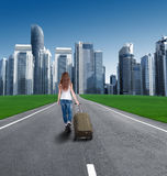 Hintere Ansicht eines Mädchens mit einem Koffer, der die Stadt kommt Lizenzfreie Stockfotografie