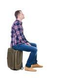 Hintere Ansicht eines Mannes, der auf einem Koffer sitzt Lizenzfreies Stockfoto