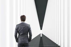 Hintere Ansicht eines Mannes in einem weißen und schwarzen Korridor Lizenzfreies Stockbild