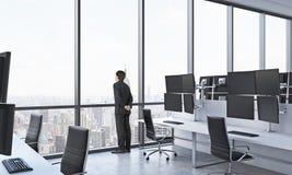 Hintere Ansicht eines Mannes im Gesellschaftsanzug, der heraus das Fenster im modernen panoramischen Büro mit New- Yorkansicht sc Stockfotografie