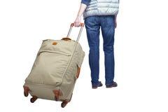 Hintere Ansicht eines Mannes mit einem Koffer auf Rädern Stockfotos