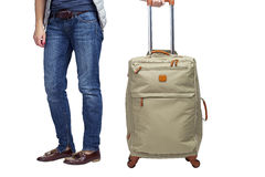 Hintere Ansicht eines Mannes mit einem Koffer auf Rädern Lizenzfreie Stockbilder