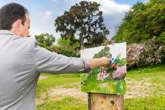 Hintere Ansicht eines Mannmalers, der draußen im Park oder im Garde arbeitet Lizenzfreies Stockbild
