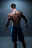 Hintere Ansicht eines schulterfreien athletischen Mannes mit Tätowierung Lizenzfreie Stockfotos