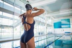 Hintere Ansicht eines Sitzschwimmers durch Pool in der Freizeitmitte Stockfotografie