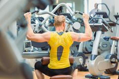Hintere Ansicht eines starken Bodybuilders mit dem Trainieren der starken Arme lizenzfreie stockbilder