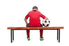 Hintere Ansicht eines traurigen kleinen Jungen im Fußballtrikot Stockfotografie