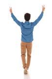 Hintere Ansicht eines zufälligen Mannes, der Sieg und das Gehen feiert Lizenzfreies Stockfoto