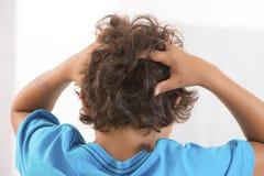 Hintere Ansicht kleiner Junge juckender Kopfhaut von den Kopfläusen Lizenzfreie Stockfotografie