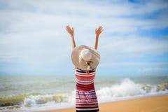Hintere Ansicht romantischer Dame Sommerstrand und -sonne genießend, bewegend in Meer wellenartig Stockfoto