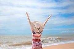 Hintere Ansicht romantischer Dame Sommerstrand und -sonne genießend, bewegend in Meer wellenartig Konzept des Gefühls und der Fre Stockfotografie