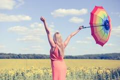 Hintere Ansicht schöner junger Dame, die draußen mehrfarbigen Regenschirm im Sonnenblumenfeld und im blauen Himmel hält Lizenzfreies Stockbild