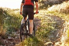 Hintere Ansicht und Nahaufnahme des jungen Radfahrerreitfahrrades auf dem Sommerfeld in der Landschaft Stockbild