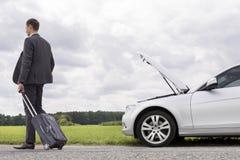 Hintere Ansicht in voller Länge des jungen Geschäftsmannes mit dem Gepäck, das aufgegliedertes Auto an der Landschaft lässt Stockfotos