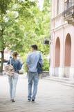 Hintere Ansicht in voller Länge von den jungen sprechenden Collegefreunden beim Gehen in Campus Lizenzfreies Stockbild