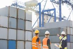 Hintere Ansicht von den Arbeitskräften, die Frachtbehälter in Versandyard kontrollieren Lizenzfreie Stockfotos