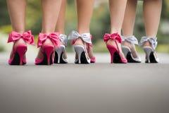 Hintere Ansicht von den Damen einer Gruppe, die bunte Bogenhohe absätze tragen Stockfoto