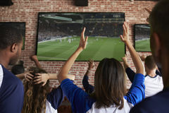 Hintere Ansicht von den enttäuschten Freunden, die Spiel in der Sport-Stange aufpassen Lizenzfreies Stockfoto