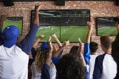 Hintere Ansicht von den Freunden, die Spiel beim Sportbar-Feiern aufpassen stockfotografie
