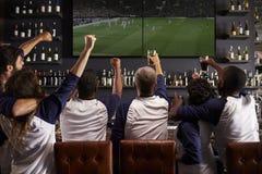 Hintere Ansicht von den Freunden, die Spiel beim Sportbar-Feiern aufpassen stockbilder