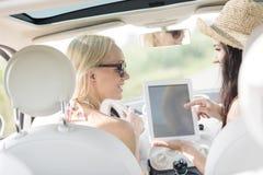 Hintere Ansicht von den glücklichen Frauen, die digitale Tablette im Auto verwenden Stockbild
