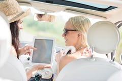 Hintere Ansicht von den glücklichen Frauen, die digitale Tablette im Auto verwenden Stockfotografie