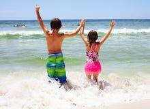 Hintere Ansicht von den glücklichen Kindern, die Arme im Wasser halten Lizenzfreie Stockfotos